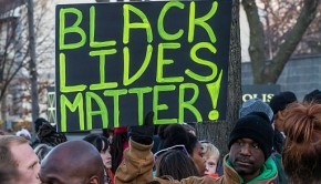 """An activist holds a """"Black Lives Matter"""" signs outside the Minneapolis Police Fourth Precinct building following the officer-involved shooting of Jamar Clark on November 15, 2015. Image from Wiki Commons for Black Lives Matter to the African Diaspora"""