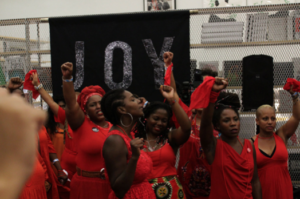 Black women artists dressed in red celebrate and testify during Simone Leigh's Waiting Room.  © Madeline Hunt 2016